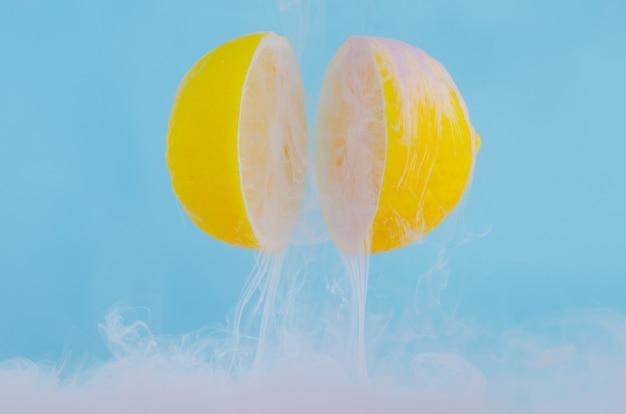 Dissolving pink poster color in water drop between two slice lemons