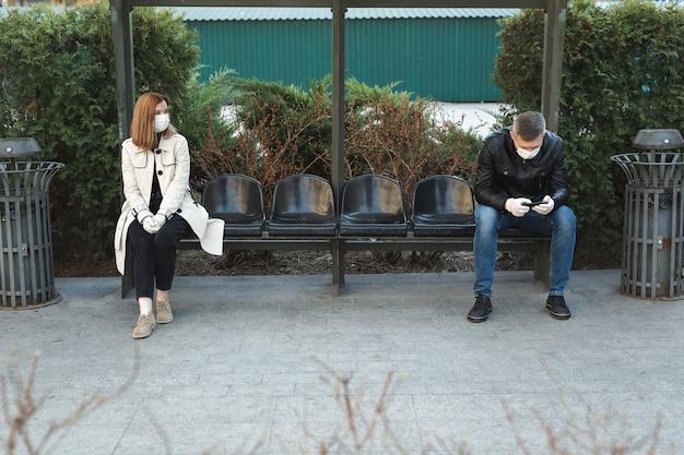 코로나 바이러스가 유행하는 동안 버스 정류장에서 남녀 사이의 거리