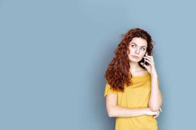 距離通信。電話をかけている間立って彼女の耳に電話を置く美しい素敵なきれいな女性