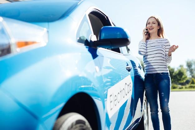 Дистанционное общение. довольная позитивная милая женщина, стоящая возле своей машины и улыбаясь во время разговора по телефону