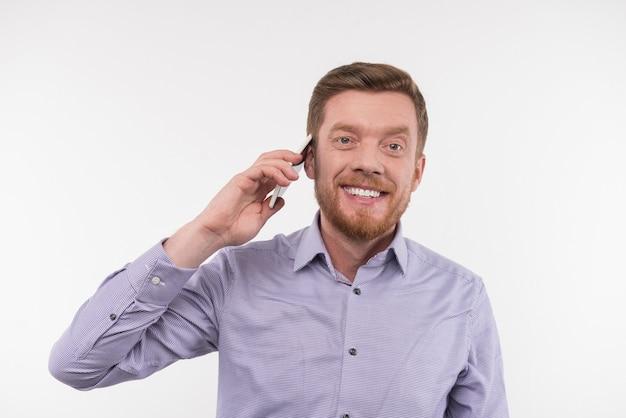 距離通信。電話をかけている間彼の耳に電話を置く幸せなひげを生やした男