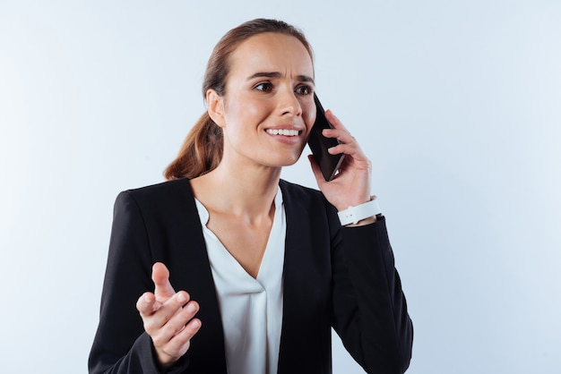 距離通信。スマートフォンを耳に当て、ビジネスについて話し合いながら電話で話している素敵な楽しい若い女性