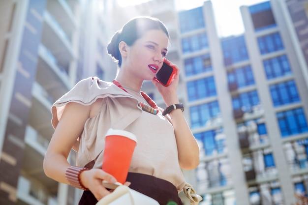 距離通信。事務所から出てしながら電話をかける快適な若い女性