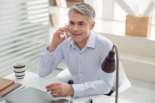 距離通信。テーブルに座って、オフィスで働いている間電話をかける前向きな喜びのいい男