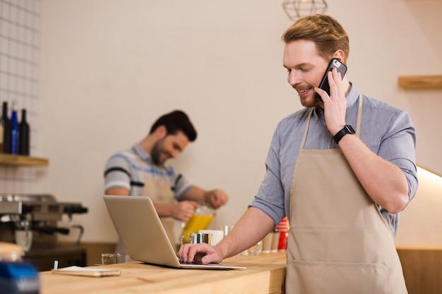 距離通信。ノートパソコンの画面を見て、ノートパソコンで作業しながら電話で話しているポジティブなうれしそうなナイスマン