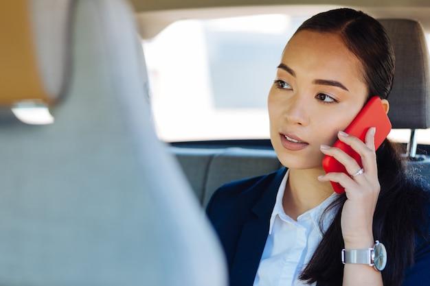 距離通信。会話をしながら彼女の耳に電話を置く賢い若い女性