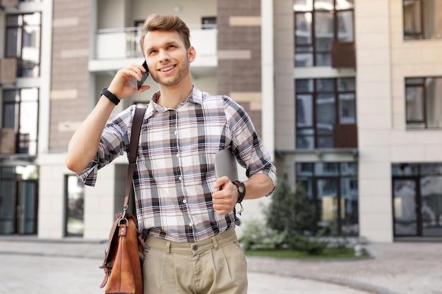 距離接続。電話をかけている間彼の耳に電話を置くうれしそうな格好良い男