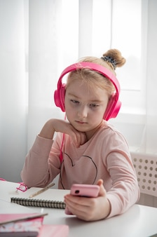 遠隔教育。インターネットを介して自宅でオンラインレッスン中に宿題を勉強しているピンクのヘッドフォンの女子高生。検疫中の社会的距離