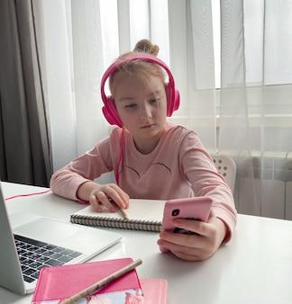 원격 교육. 인터넷을 통해 집에서 온라인 수업 중 숙제를 공부하는 분홍색 헤드폰 여학생. 격리 중 사회적 거리