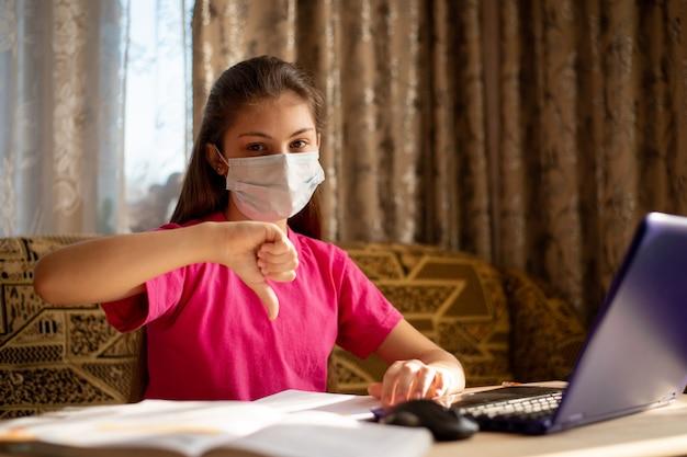 遠隔教育。自宅で座って親指を下に向けたジェスチャーを示す医療マスクの苦しめられた少女、コロナウイルスの検疫中に遠隔学習をすること