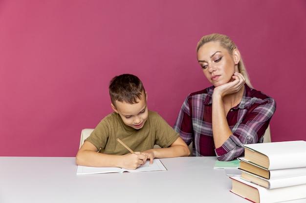 원격 교육. 어머니는 미취학 아동이 수업을하도록 도와줍니다. 격리시 교육