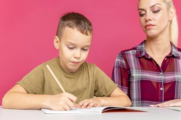 一緒に遠隔教育。家で一緒に宿題をしている息子と一緒のお母さん。