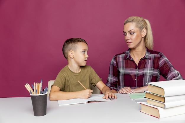 Дистанционное домашнее задание с мамой дома на время карантина. мальчик с мамой сидит за столом и учится.