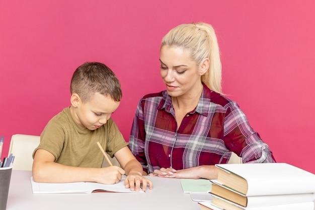 検疫時に自宅で母親との距離宿題。机に座って勉強しているお母さんと男の子。