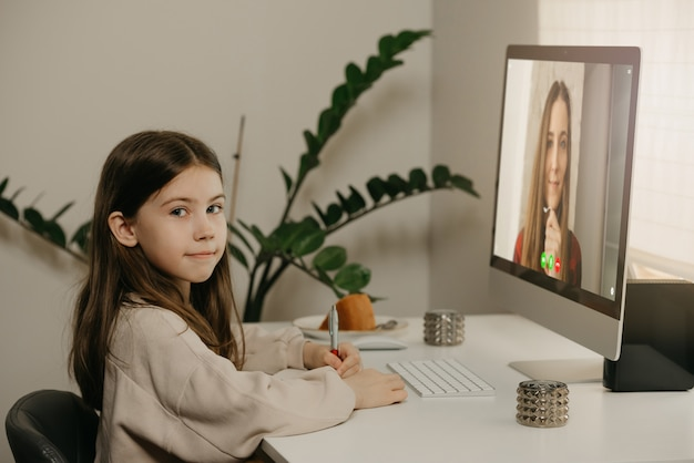 원격 교육. 긴 머리는 그녀의 남성 교사 온라인에서 원격으로 공부와 함께 어린 소녀. 예쁜 여자 아이는 집에서 데스크톱 컴퓨터를 사용하여 수업을 배웁니다. 가정 교육.