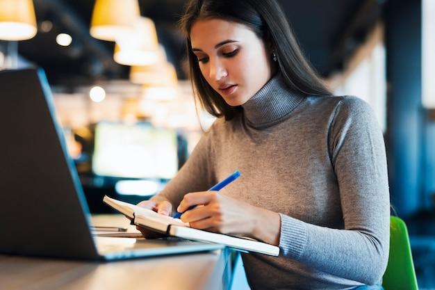通信教育。白いシャツを着た美しい笑顔の女性がノートパソコンの前で動作します。