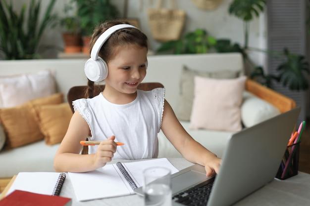 通信教育。オンラインeラーニングシステムを介して勉強しているラップトップを使用してヘッドフォンで陽気な女の子の女の子。