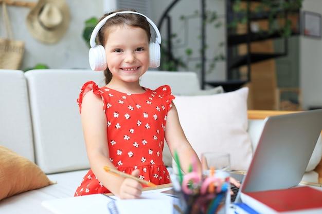 通信教育。オンラインeラーニングシステムを介して勉強しているラップトップコンピューターを使用して陽気な少女。