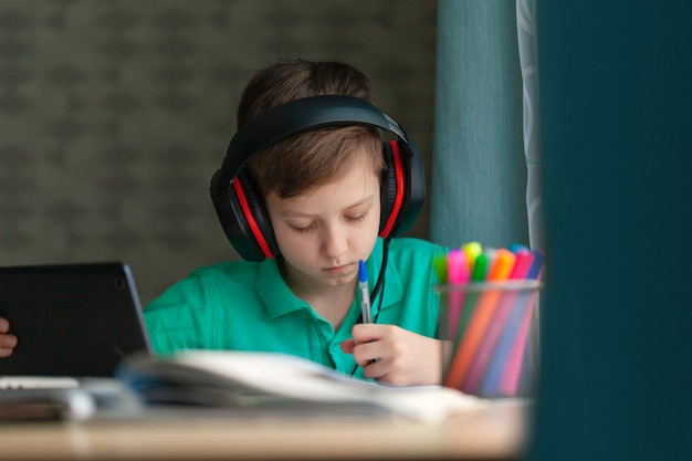 Distance learning child writting homework with digital tablet. concept online education.