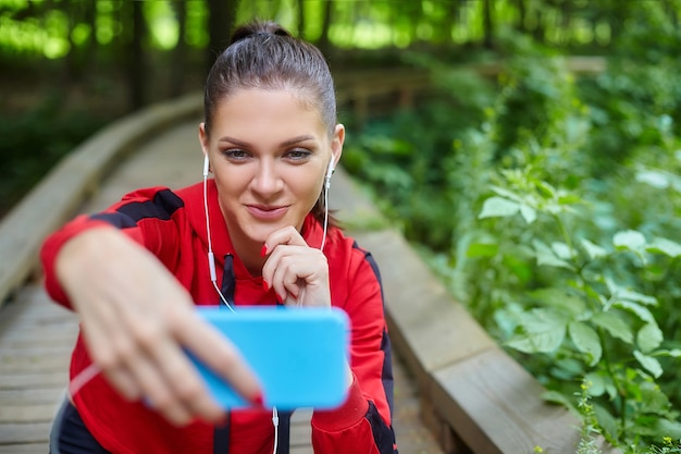 원격 학습 개념. 스포츠웨어에 매력적인 여자는 삼림 공원에서 나무 경로에 앉아있다. 스마트 폰을 통한 온라인 레슨.