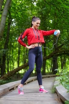 원격 학습 개념. 스포츠웨어에 매력적인 여자는 삼림 공원에서 나무 경로에 선다. 스마트 폰을 통한 온라인 레슨.