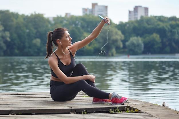 Концепция дистанционного обучения. привлекательная девушка в спортивной одежде сидит на деревянном пирсе в городском парке. онлайн-уроки через смартфон.
