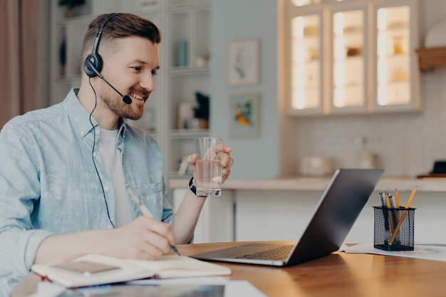 Distance learning concept. millennial guy student in headset watches webinar has online lessons during quarantine enjoys internet education drinks water from glass makes notes poses at desktop