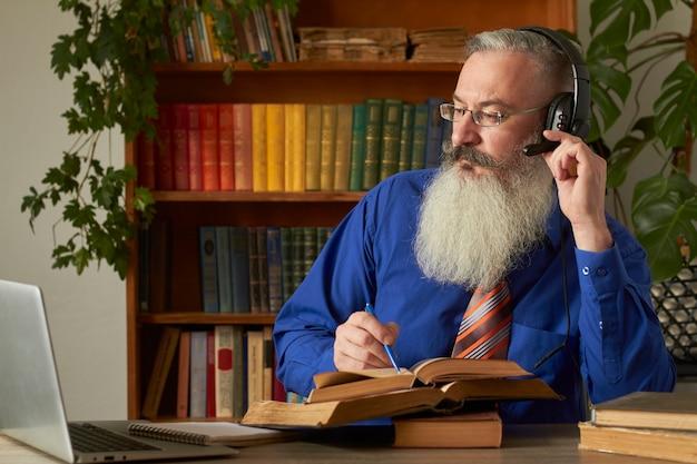 遠隔学習のコンセプト。教師の先生の家庭教師は規律をオンラインで教えます。成熟したひげを生やした男はラップトップを介して先生の質問に答えます。