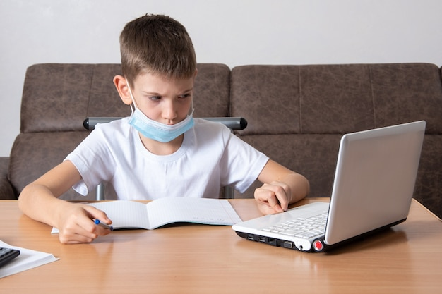 전염병 중 원격 학습 - 얼굴에 보호 마스크를 쓴 진지한 남학생이 노트북을 보고, 노트북에 정보를 쓰고, 집에 있는 테이블에 앉아 있습니다. 학교 개념으로 돌아가기