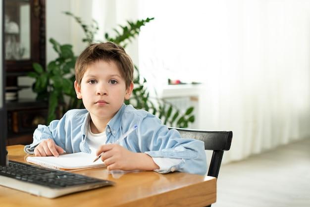 隔離中の隔離中の遠隔学習。少年と自宅のラップトップ。ライフスタイル。ゲーム中毒。オンラインゲーム