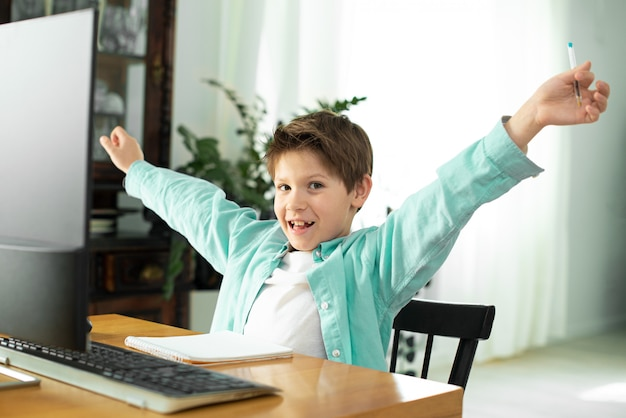 コロノウイルスの隔離中の隔離中の遠隔学習。少年と自宅のラップトップ。ライフスタイル。ゲーム中毒。オンラインゲーム。感情