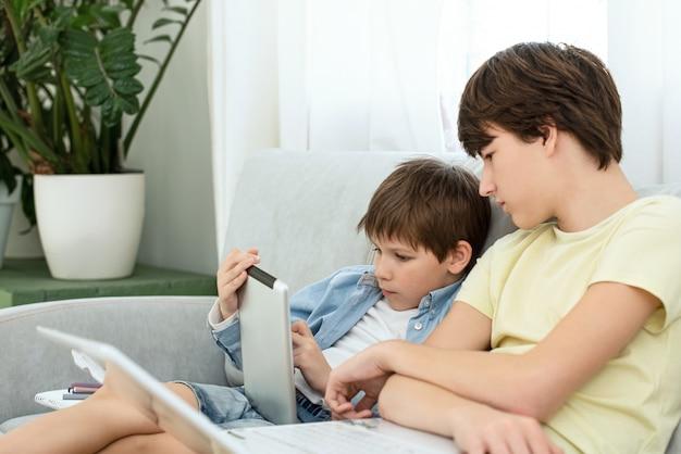 Дистанционное обучение во время изоляции во время карантина на короновирус. мальчик и ноутбук у себя дома.