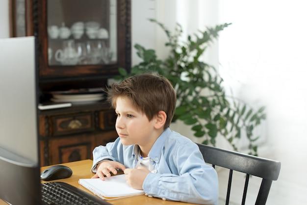 コロノウイルスの隔離中の隔離中の遠隔学習。少年と自宅のラップトップ。