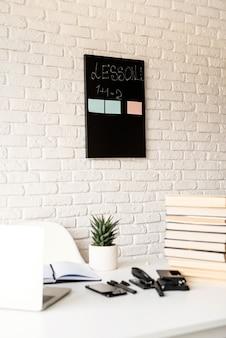 Дистанционное обучение. электронное обучение. легкое и просторное рабочее место, учительский стол с ноутбуком, книги и канцелярские товары, акцент на фоне