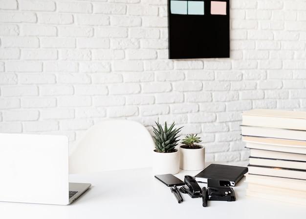 Дистанционное обучение. электронное обучение. легкое и просторное рабочее место, учительский стол с ноутбуком, книги и канцелярские принадлежности, акцент на переднем плане