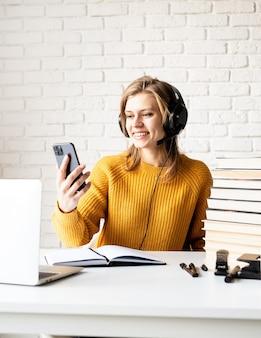 通信教育。 eラーニング。携帯電話を探しているラップトップを使用してオンラインで勉強している黒いヘッドフォンで若い笑顔の女性