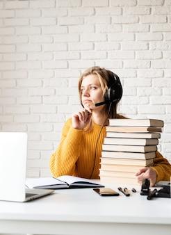 通信教育。 eラーニング。ノートに書くラップトップを使用してオンラインで勉強している黒いヘッドフォンで若い笑顔の女性