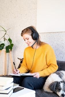 원격 교육. e- 러닝. 집에서 소파에 앉아 노트북을 사용하여 온라인으로 공부하는 노란색 스웨터와 검은 헤드폰에 젊은 웃는 여자
