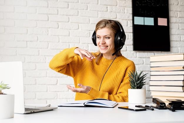 원격 교육. e- 러닝. 화상 채팅에서 이야기하는 노트북을 사용하여 온라인으로 공부하는 노란색 스웨터와 검은 헤드폰에 젊은 웃는 여자