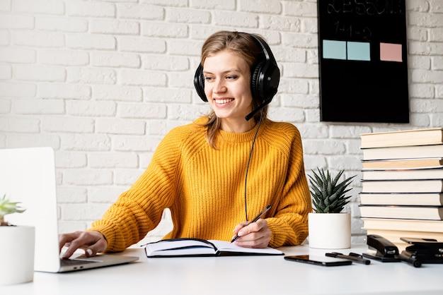 원격 교육. e- 러닝. 노란색 스웨터와 노트북에 쓰는 노트북을 사용하여 온라인으로 공부하는 검은 헤드폰에 젊은 웃는 여자
