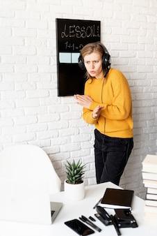원격 교육. e- 러닝. 노트북에서 화상 채팅을 사용하여 온라인으로 가르치는 노란색 스웨터와 검은 헤드폰에 젊은 웃는 여자
