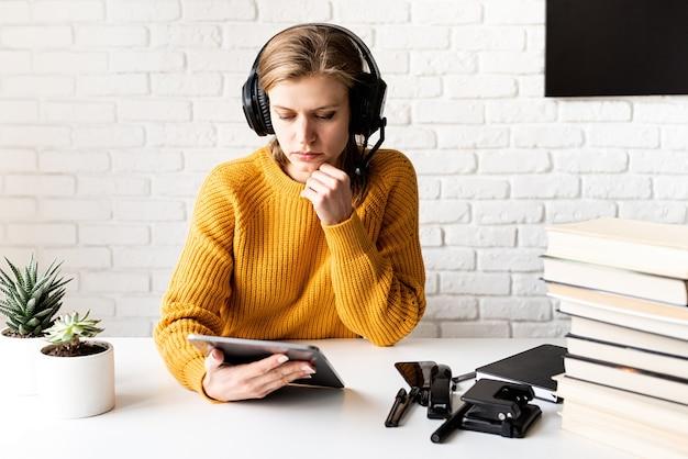 원격 교육. e- 러닝. 노란색 스웨터와 디지털 태블릿을 사용하여 온라인으로 공부하는 검은 헤드폰에 젊은 사려 깊은 여자
