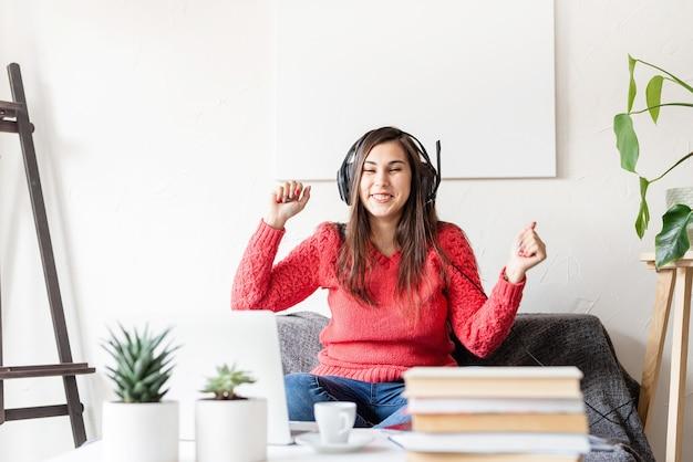 通信教育。 eラーニング。赤いセーターと黒いヘッドフォンでソファに座って踊る若い女性