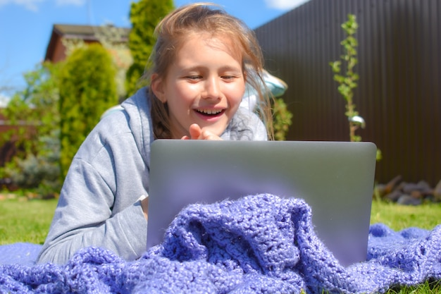 Distance learning. a girl is studying remotely outdoor in park. home education.