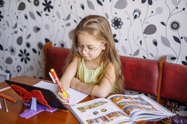 원격 교육. 가정 온라인 학습. 어린 소녀는 영어를 가르치고 온라인으로 교사와 이야기합니다.