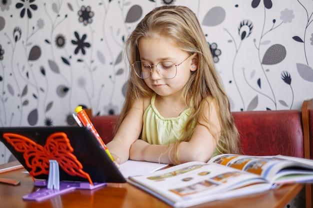 通信教育。ホームオンライン学習。小さな女の子は英語を教え、オンラインで先生と話します。