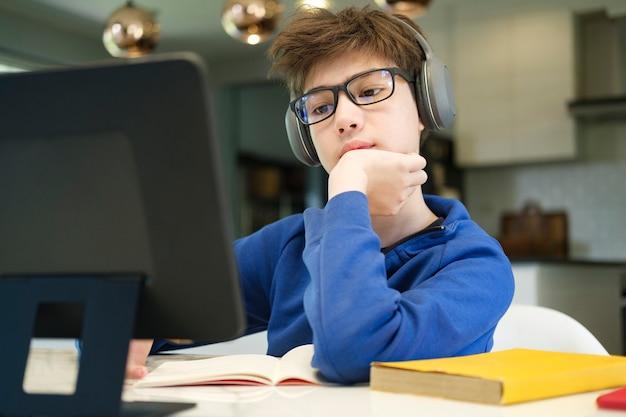 원격 학습 온라인 교육. 남학생은 집에서 공부하고 학교 숙제를 합니다. 가정 원격 학습입니다.