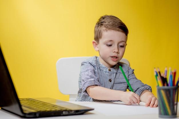 Дистанционное обучение онлайн. школьник учится дома и делает домашнее задание