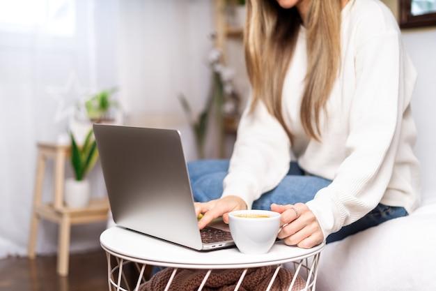 원격 교육 온라인 교육 및 업무. 식물 근처 소파에 앉아 노트북에 입력하는 커피 컵과 비즈니스 여자.