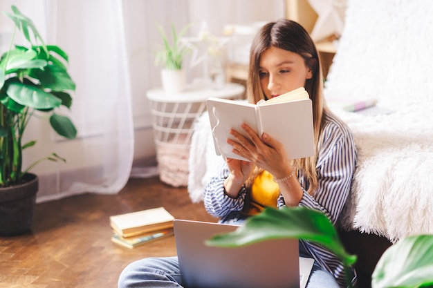 원격 교육 온라인 교육 및 업무. 비즈니스 우먼 바닥에 앉아 노트북에 씁니다.